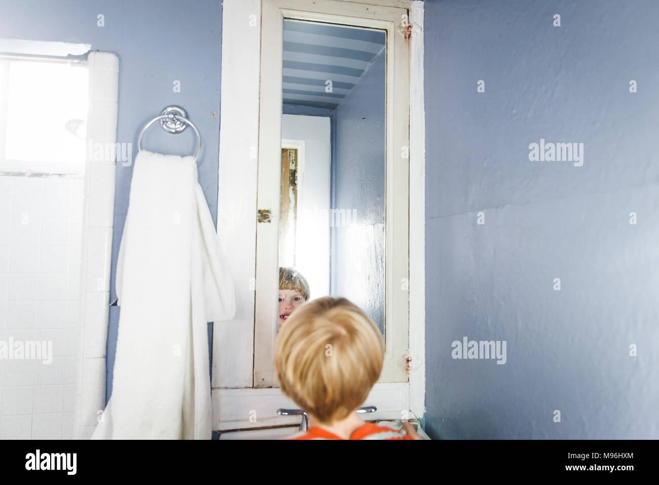 Junge lächelnd an sich selbst in den Spiegel Stockbild