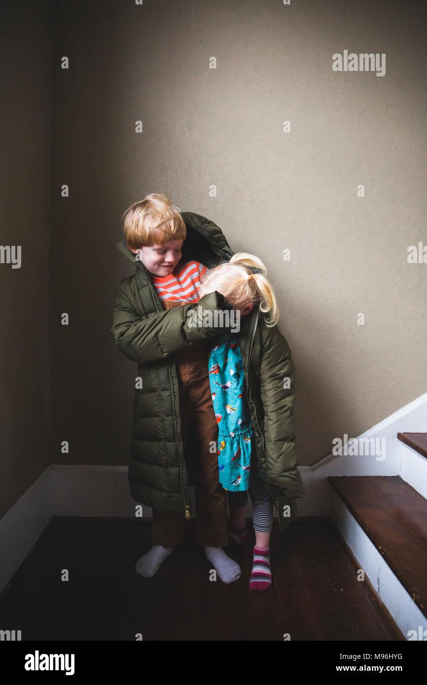 Junge und Mädchen in überdimensionalen Jacke Stockbild