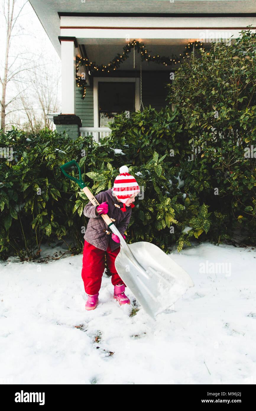 Mädchen große Schaufel Schnee bewegen Stockbild