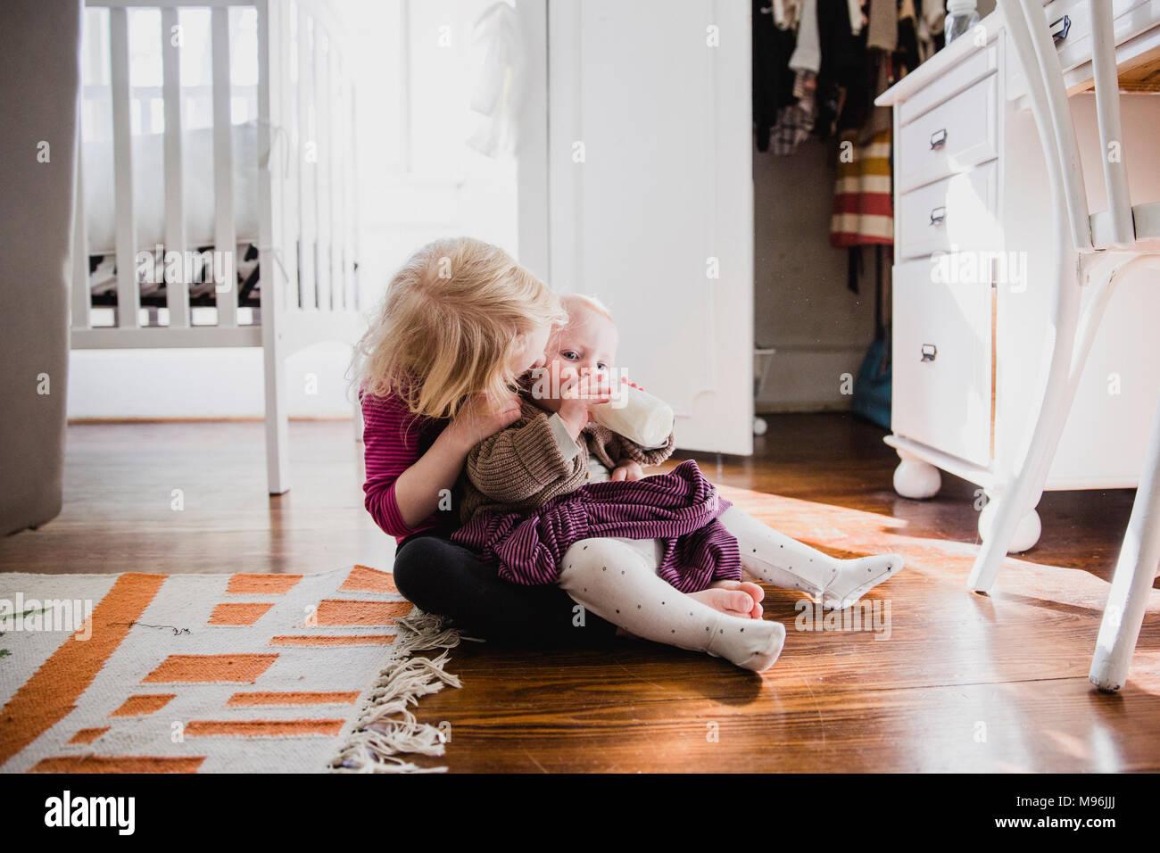 Mädchen mit Baby auf dem Schoß Stockbild