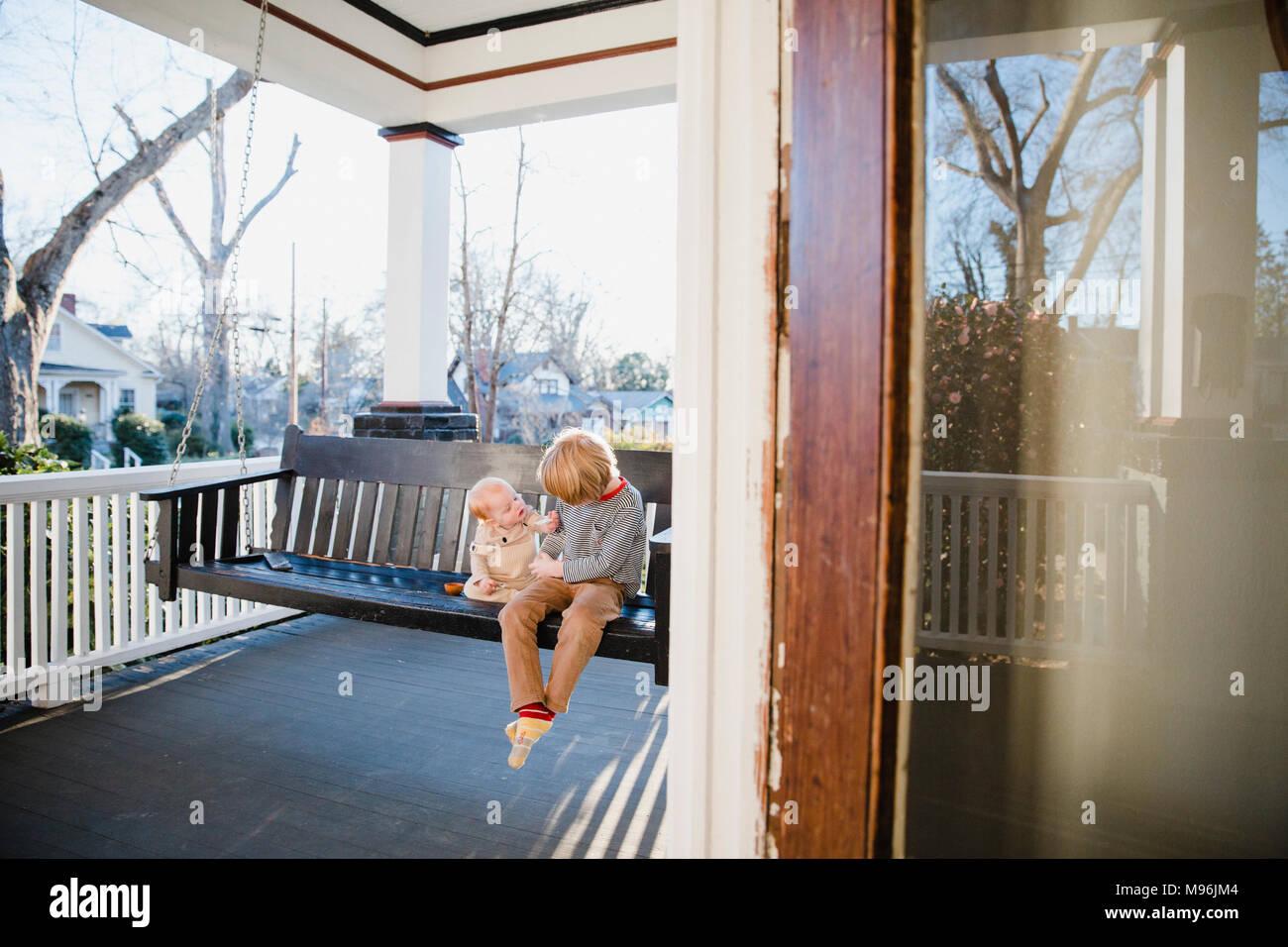 Baby und junge auf schwingen Sitzbank Stockbild
