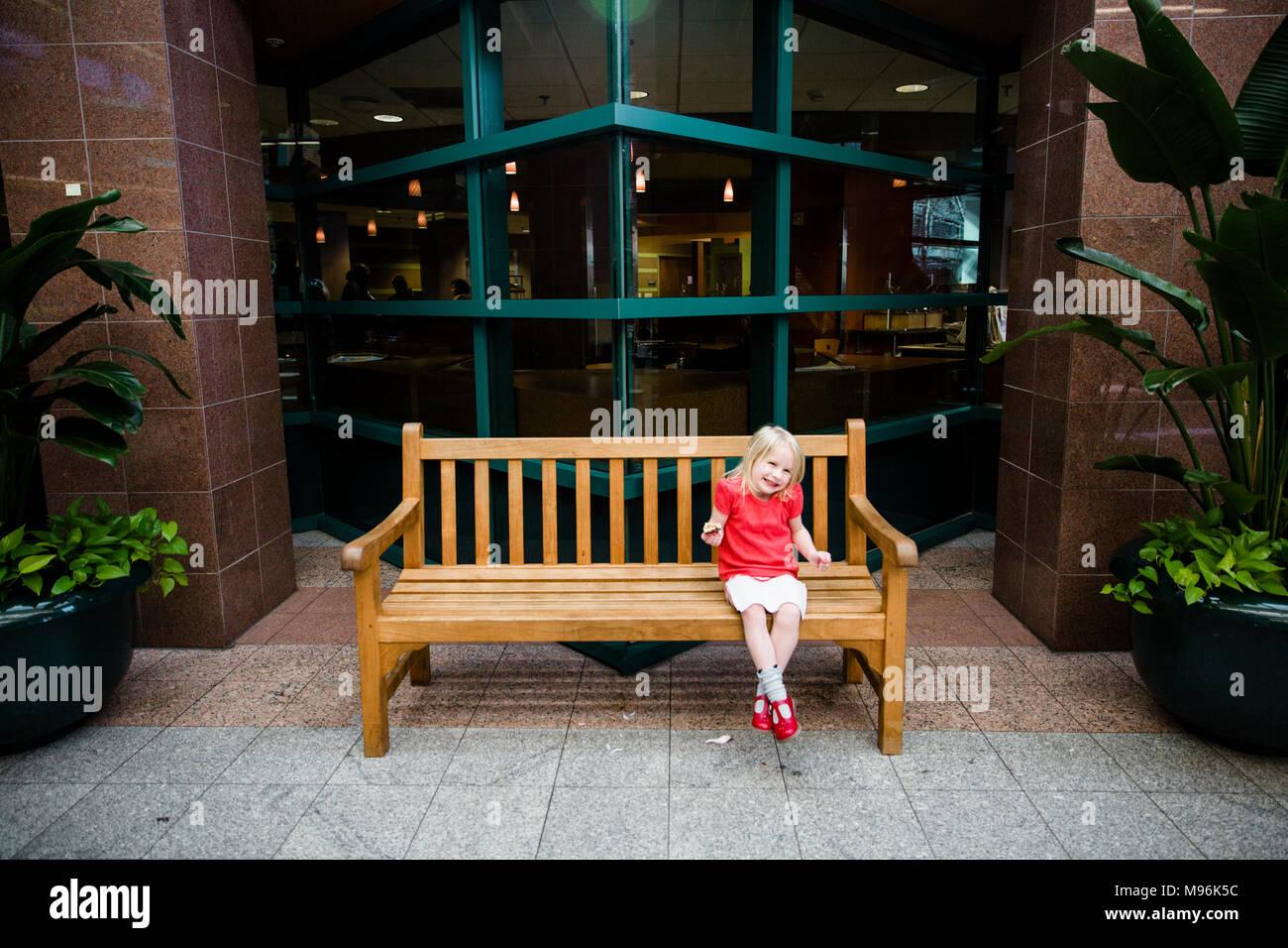 Mädchen im roten Hemd sitzt auf holzbank Stockbild