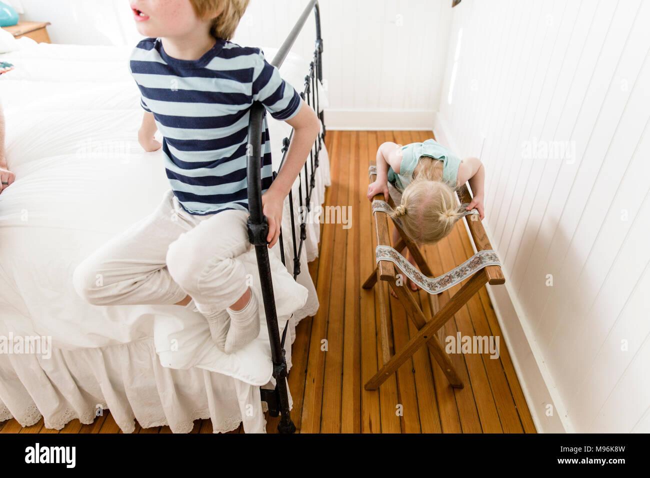 Mädchen schauen durch Klappstuhl mit Junge auf dem Bett neben ihr Stockbild