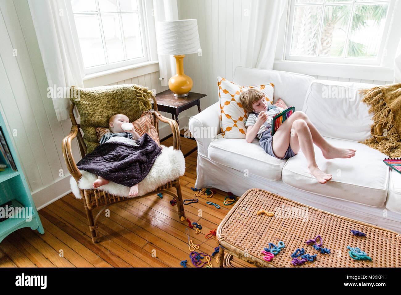 Junge Verlegung auf Sofa Lesung mit Baby neben ihm Stockbild