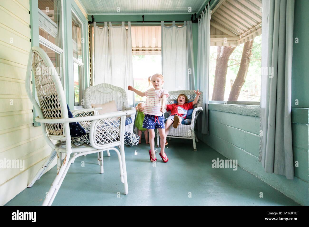 Jungen und zwei Mädchen spielen im Freien Stockbild