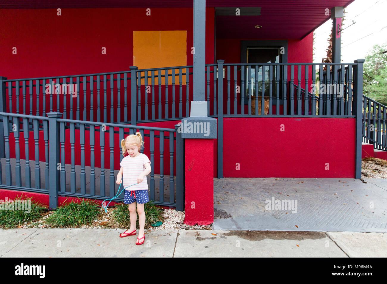 Mädchen außerhalb der roten Gebäude Stockbild