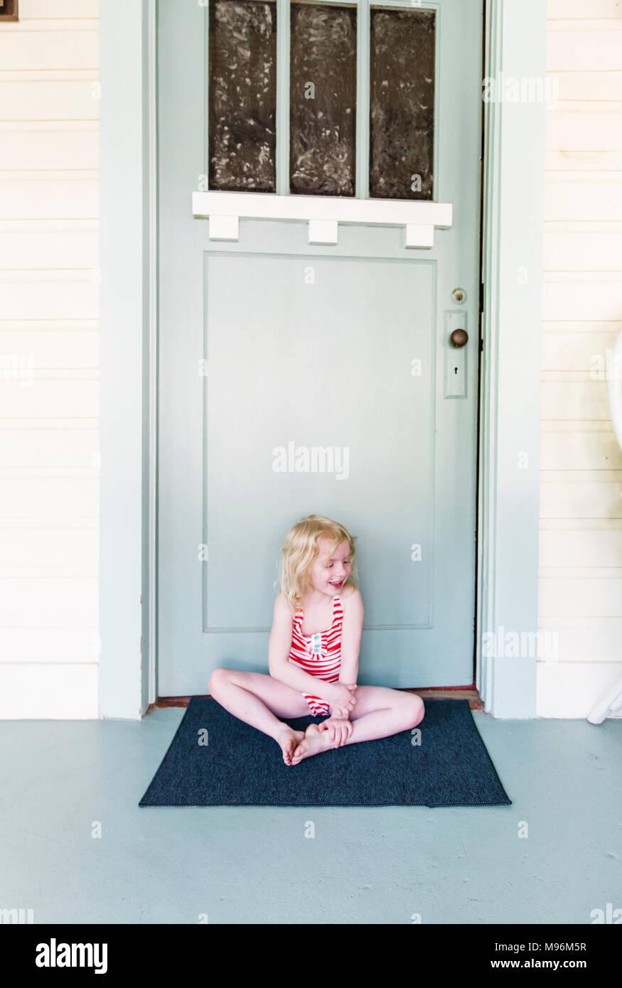 Mädchen lächelnd/Sitzung außerhalb der Tür Stockbild