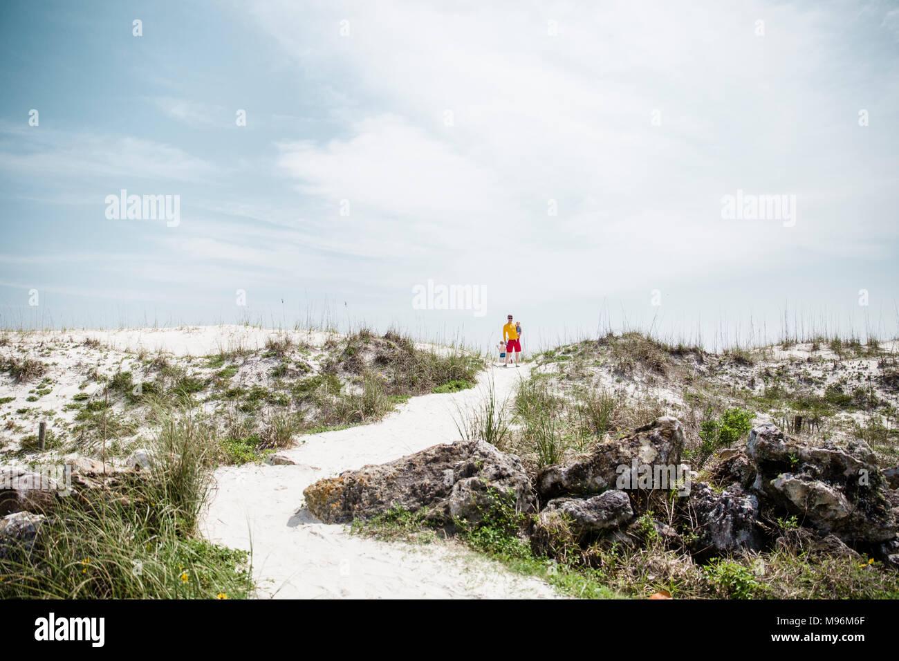 Familie zu Fuß rund um den Strand Stockbild
