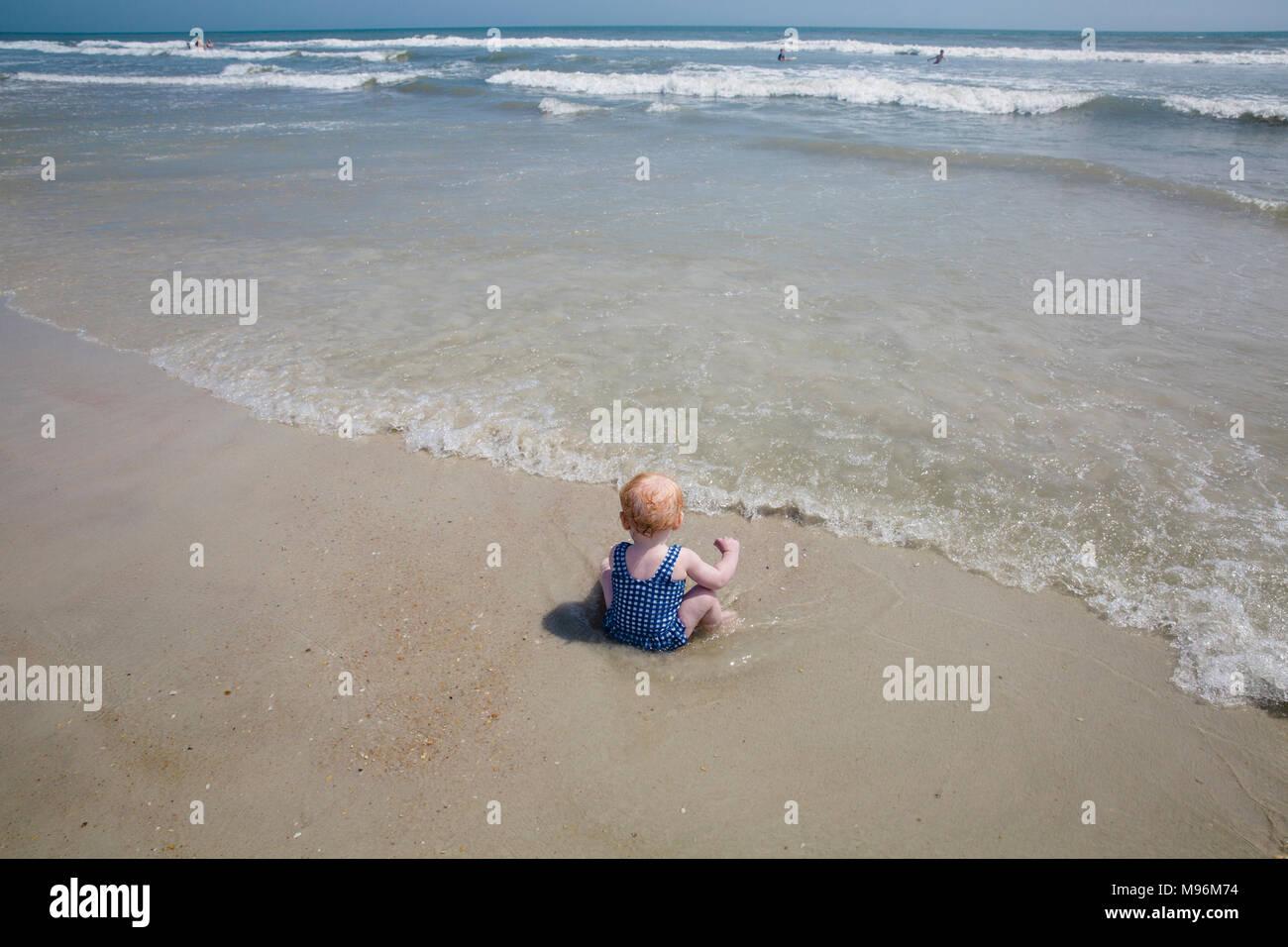Baby im Wasser sitzen am Strand. Stockbild
