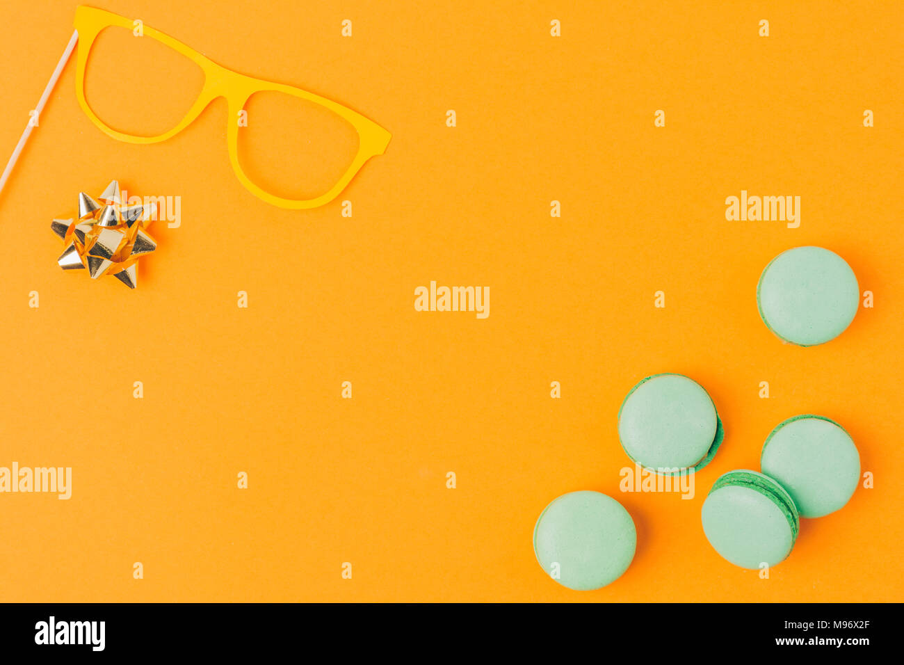 Blick von oben auf die Party Maske, Bogen und macarons auf Orange, purim Urlaub Konzept isoliert Stockbild
