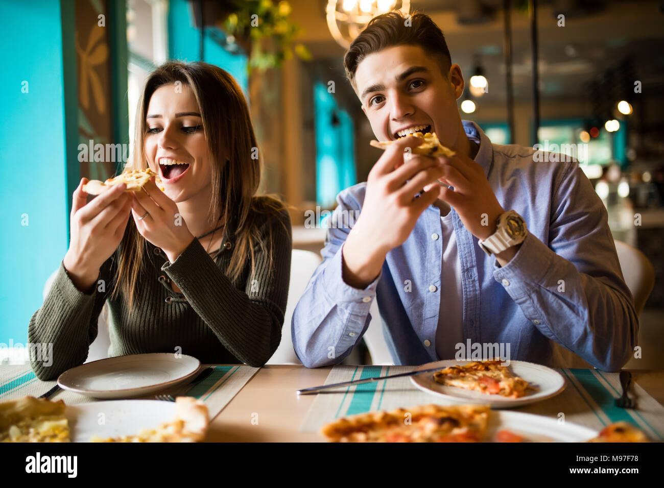 Schließen Sie herauf Foto der jungen Paare genießen in Pizza, zusammen Spaß zu haben. Konsum, Nahrung, Lifestyle Konzept Stockbild