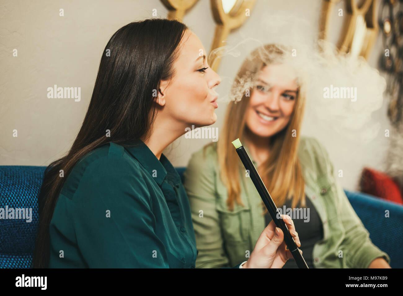 Zwei glückliche Frauen sitzen im Shisha Bar und Rauchen nargile Stockbild