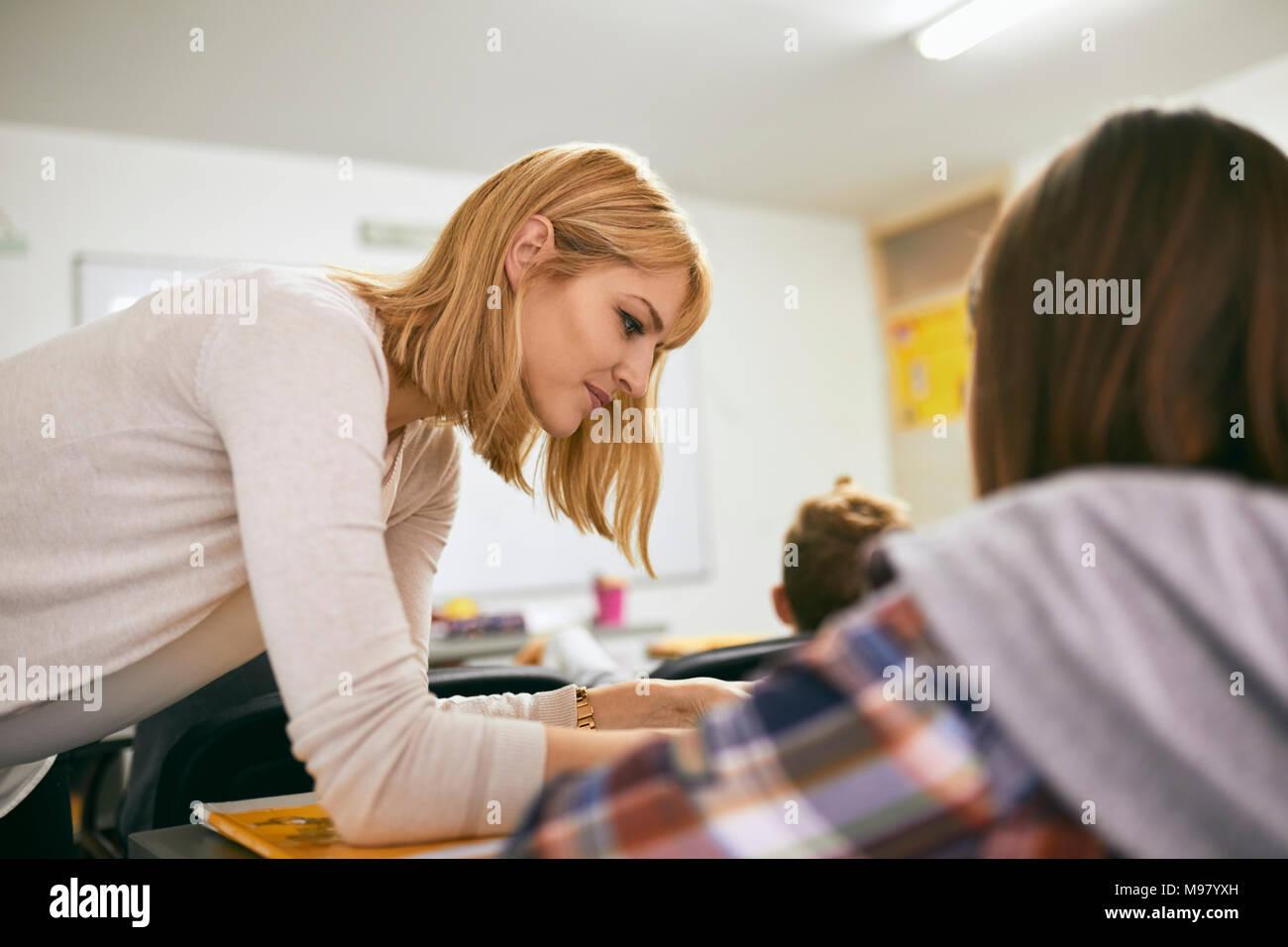 Lehrer helfen, Student am Schreibtisch in der Klasse Stockbild
