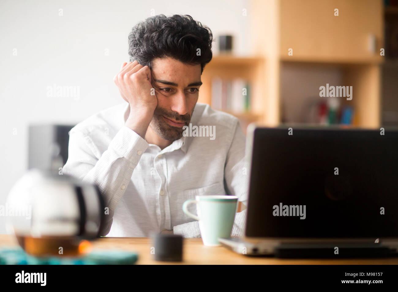 Portrait von Geschäftsmann am Schreibtisch, Laptop Stockbild