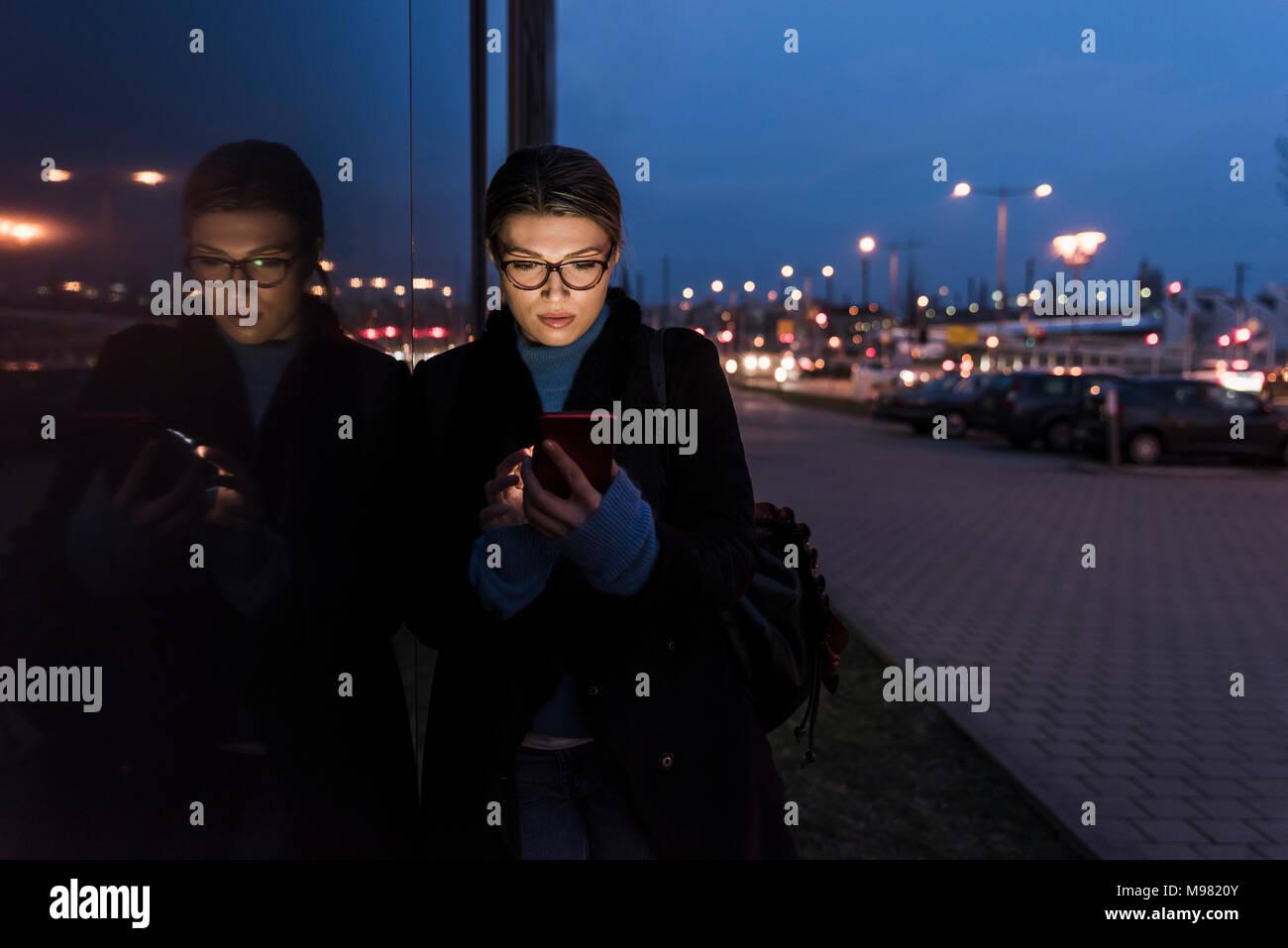 Junge Frau lehnte sich gegen die Glasfront in der Nacht über Mobiltelefon Stockbild