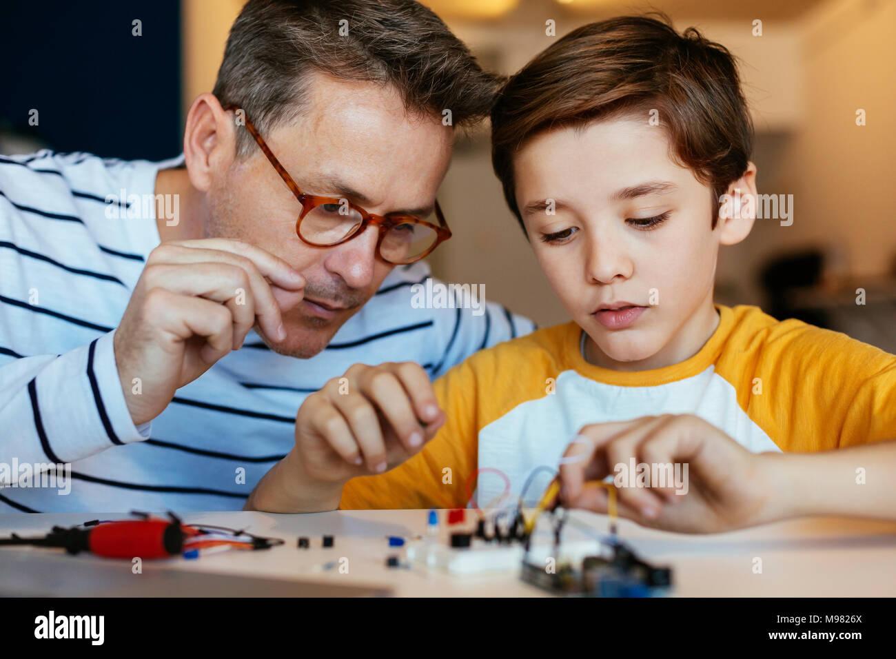 Vater und Sohn der Zusammenstellung eines elektronischen Baukasten Stockbild
