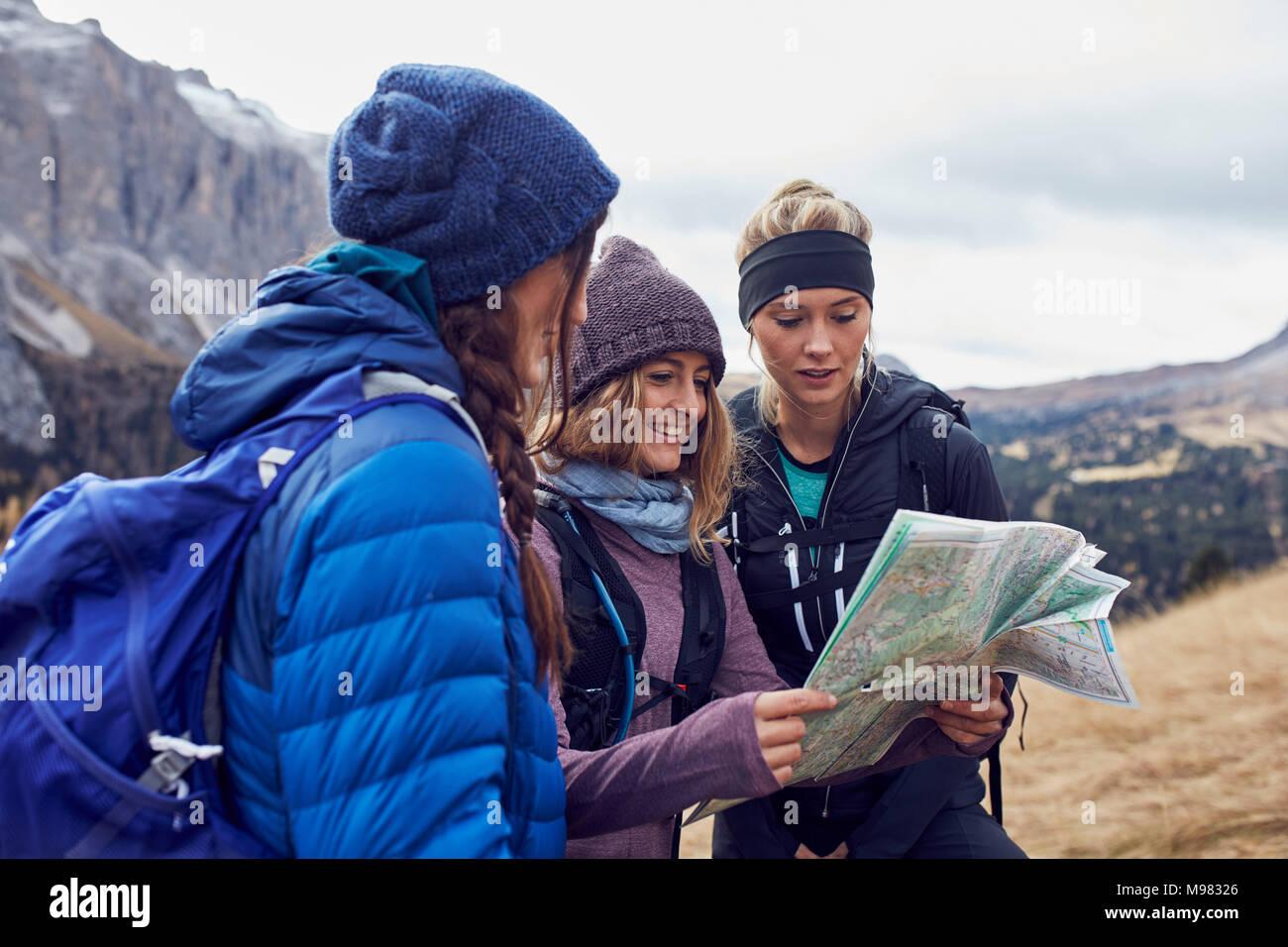 Drei junge Frauen wandern in den Bergen und auf der Karte suchen Stockbild