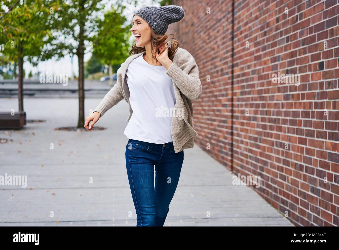Glückliche Frau, die auf der Straße Stockbild