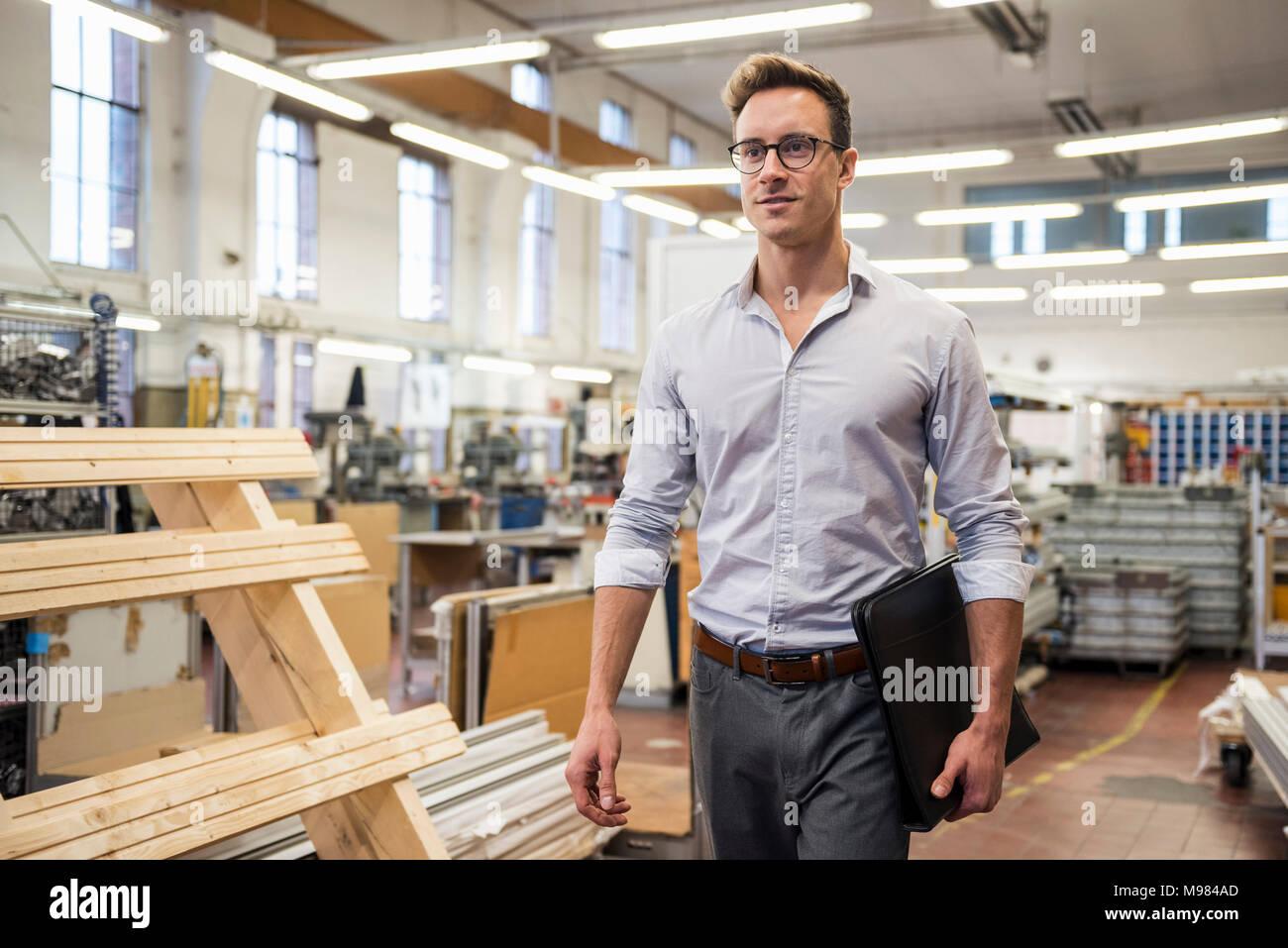 Junge Unternehmer gehen in Fabrik Ordner um: Stockbild