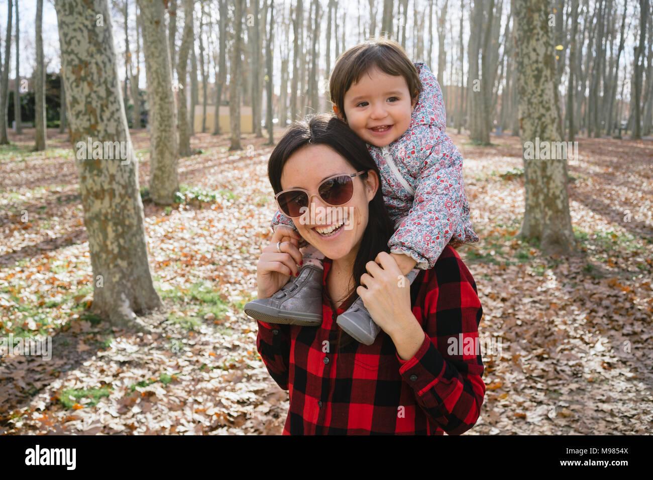 Die Mutter ihre Tochter tragen auf ihren Schultern in Park Stockbild