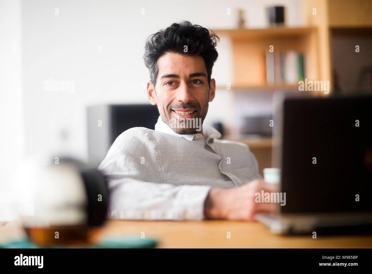 Portrait von entspannt Geschäftsmann am Schreibtisch Stockbild