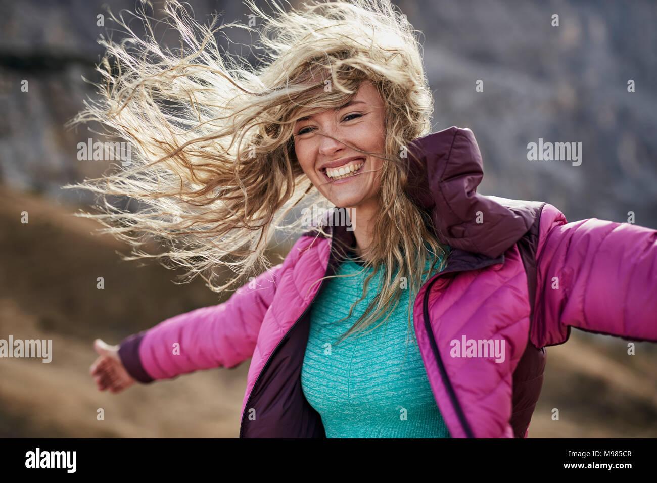Glückliche junge Frau gegen den Wind in den Bergen schiefen Stockbild