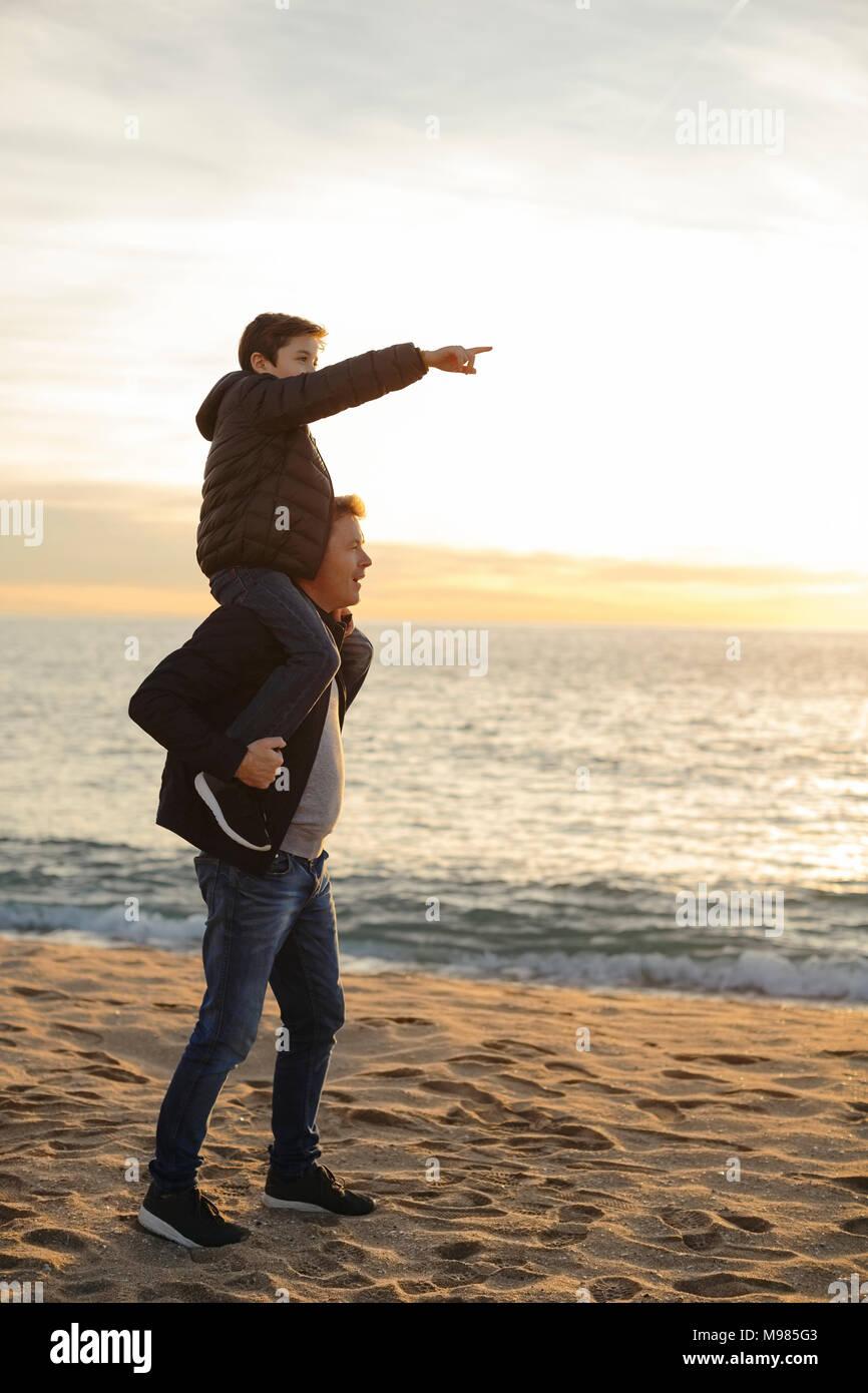 Vater mit Sohn Huckepack am Strand bei Sonnenuntergang Zeigefinger Stockbild