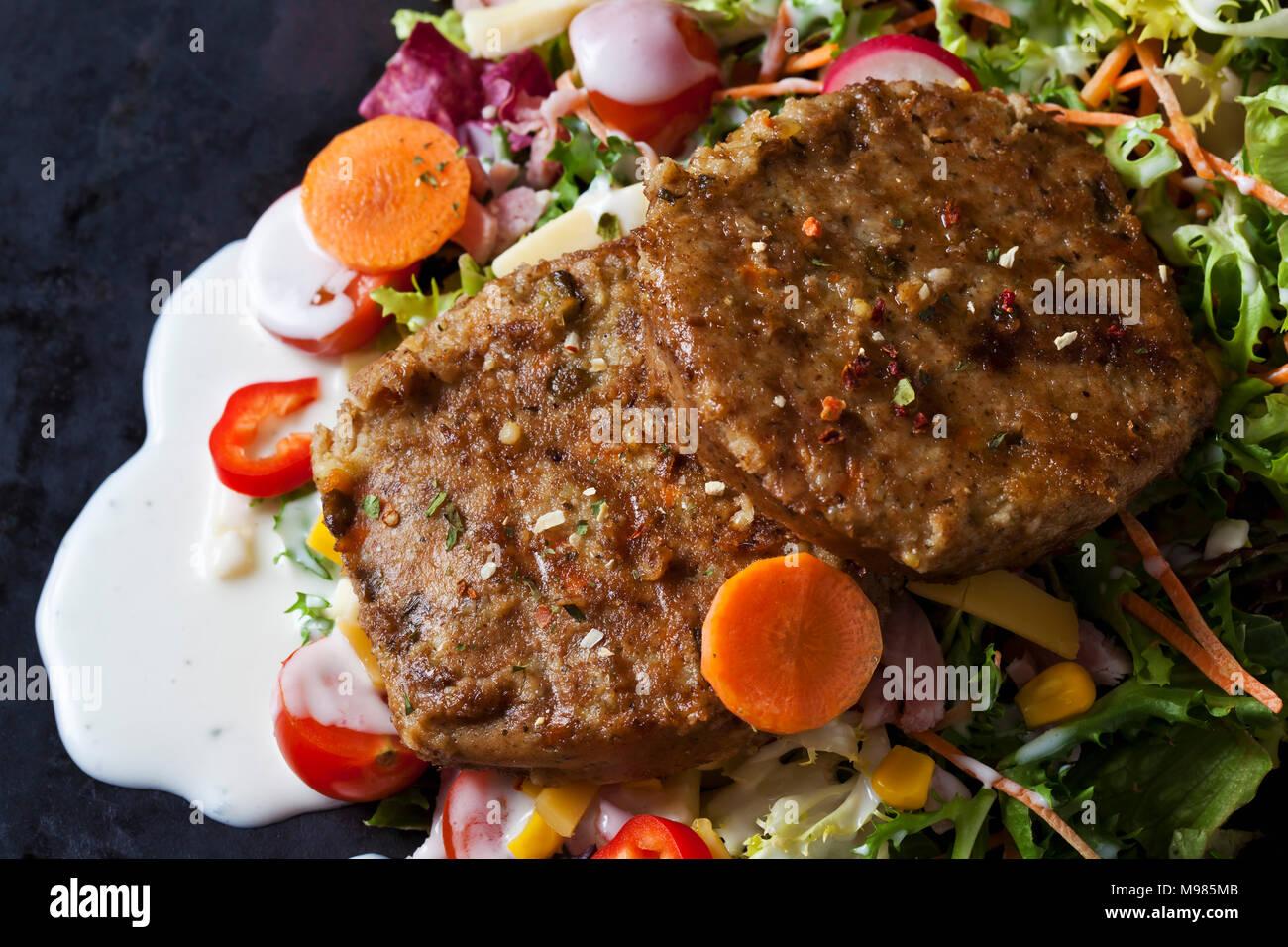 Veggie Burger mit Salat, Gemüse und Joghurt Sauce Stockbild