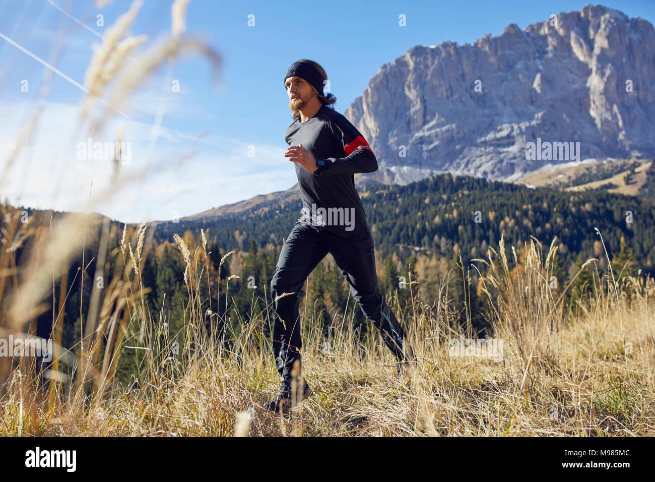 Mann läuft auf Bergweg Stockfoto