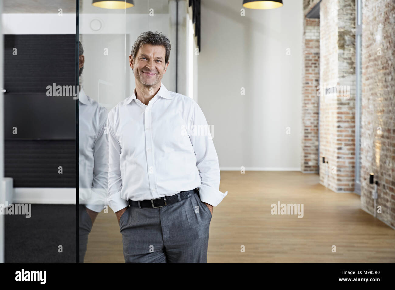 Portrait von lächelnden Geschäftsmann lehnte sich gegen Glasscheibe in modernen Büro Stockfoto