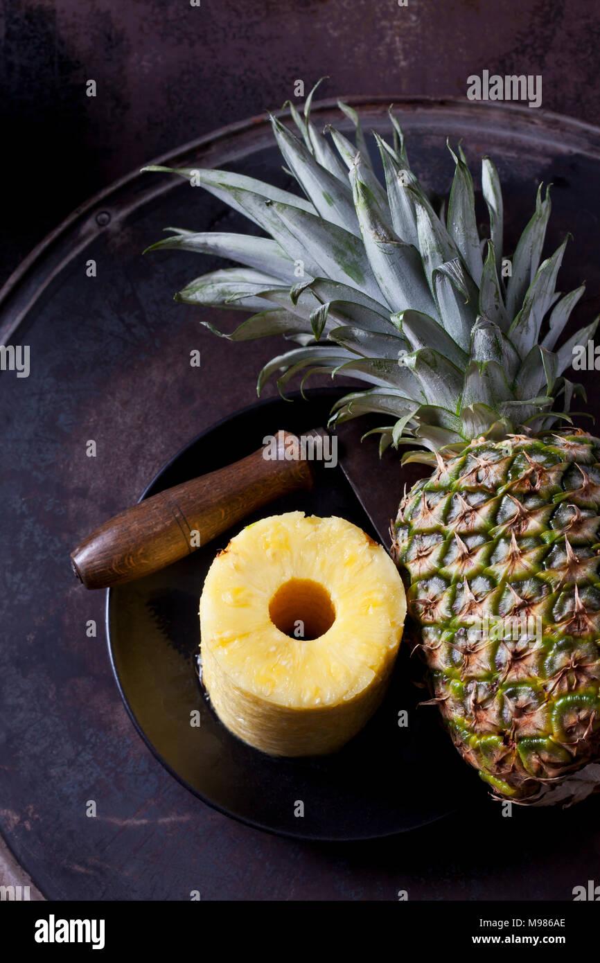 Stapel von Scheiben Ananas, ganze Ananas und Cleaver Stockbild