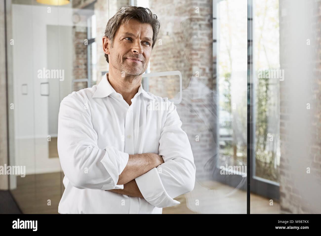 Portrait von Reifen Geschäftsmann lehnte sich gegen Glasscheibe in modernen Büro Stockfoto