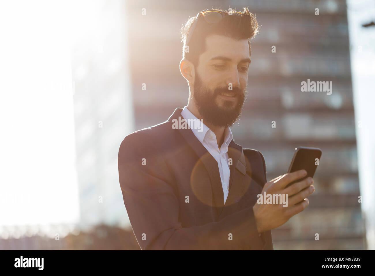 Geschäftsmann mit Handy vor Bürogebäude Stockbild