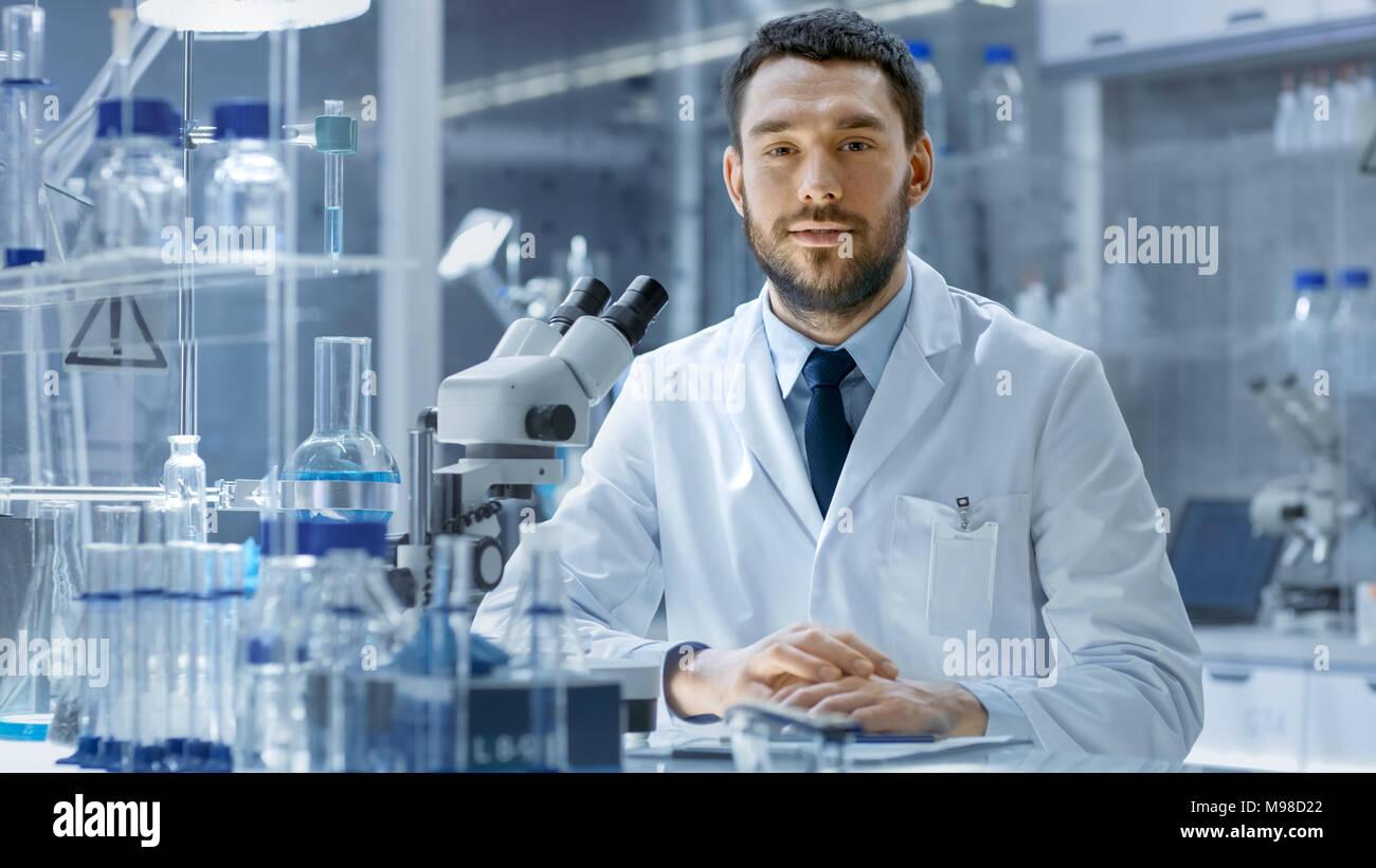 Junge männliche Forschung sieht in die Kamera und lächelt. Er sitzt in einem High-End-modernes Labor mit Becher, Gläser, Mikroskop und funktionierenden Bildschirm Stockfoto