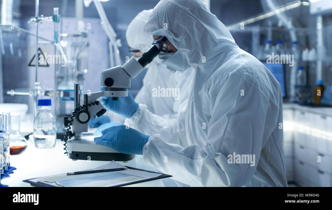 In einem sicheren Hohe Labor Wissenschaftler in einem Overall, die Durchführung einer Forschung. Chemiker untersucht Proben unter dem Mikroskop und Kollege Ergebnisse Stockbild