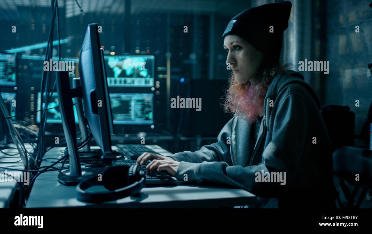 Nonkonformistische Jugendliche Hacker Mädchen mit Computer für Angriffe auf Unternehmensservern mit Malware. Das Zimmer ist dunkel, Neon und hat viele wird angezeigt. Stockbild