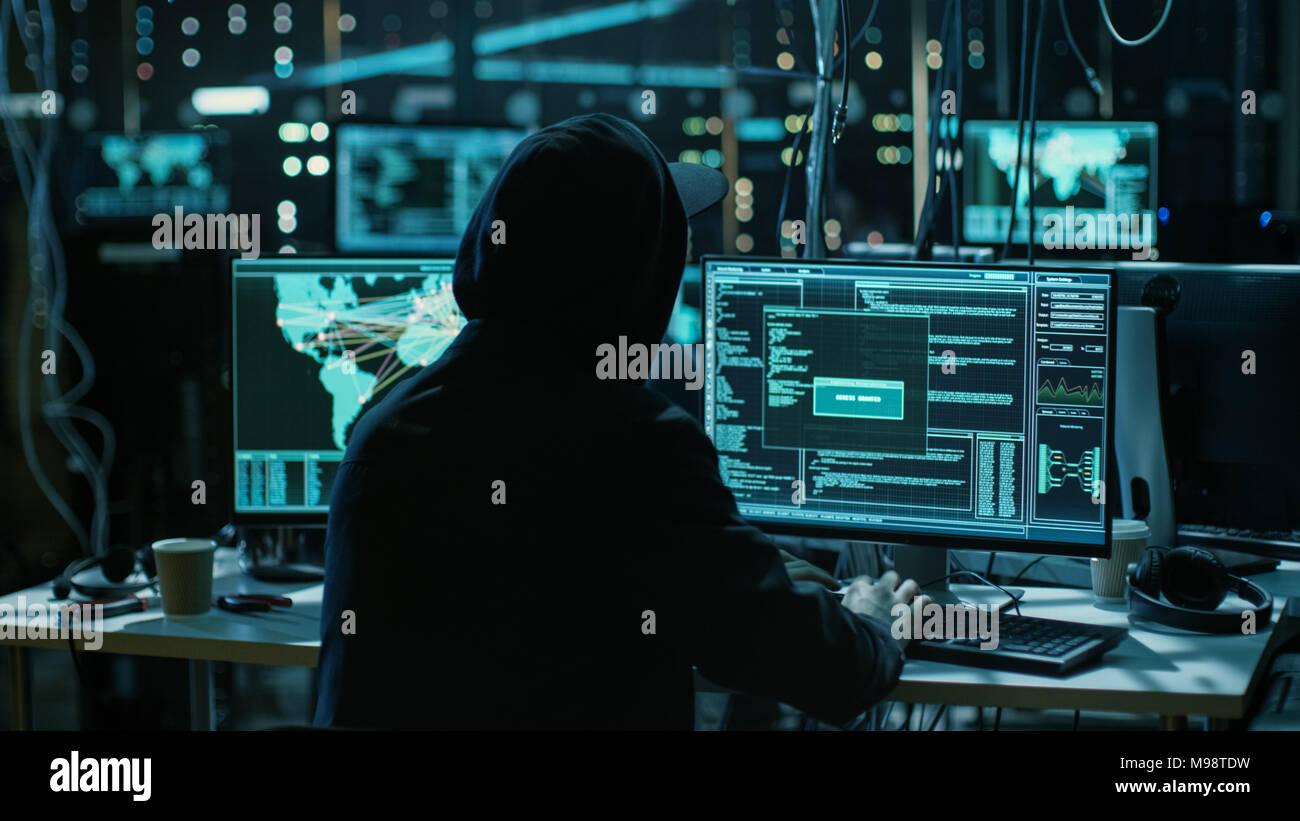 Jugendliche Hacker arbeiten mit seinem Computer infizieren, Server und Infrastruktur mit Malware. Sein Versteck ist dunkel, Neon beleuchtet und mit mehreren Anzeigen. Stockbild