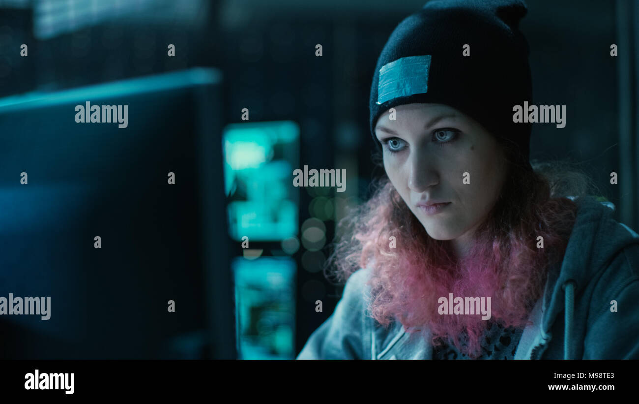 Nonkonformistische Jugendliche Hacker Mädchen mit rosa Haaren Angriffe Corporate Server mit Malware. Das Zimmer ist dunkel, Neon und hat viele wird angezeigt. Stockbild