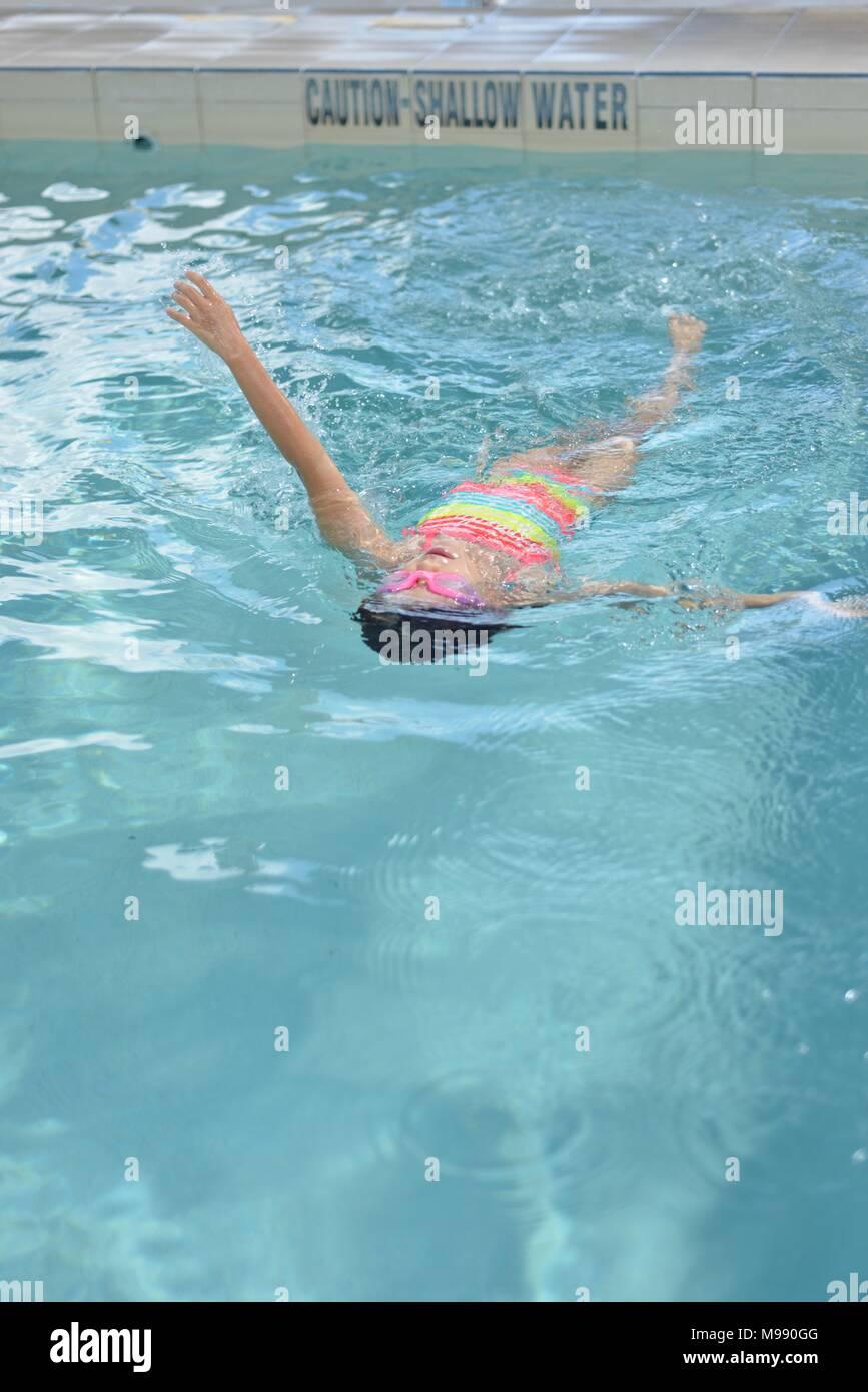 Junge Mädchen einen Rückschlag in einem öffentlichen Schwimmbad, Ausbildung, Kokoda Schwimmbad, Townsville, Queensland, Australien Stockbild