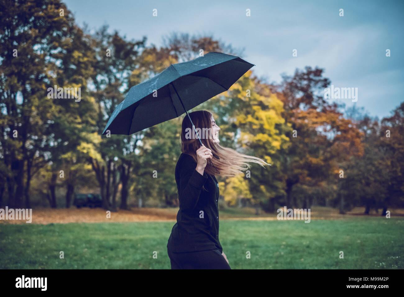 Glückliche junge Frau mit Schirm wandern in herbstlichen Park Stockbild
