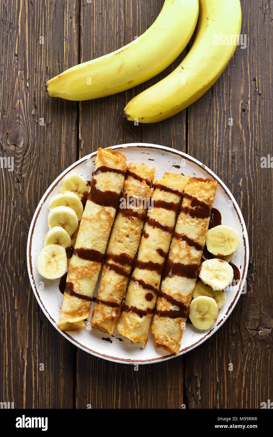 Leckere Crêpe-Rolle mit Bananenscheiben und Schokoladensauce auf Holz- Hintergrund. Ansicht von oben, flach Stockbild