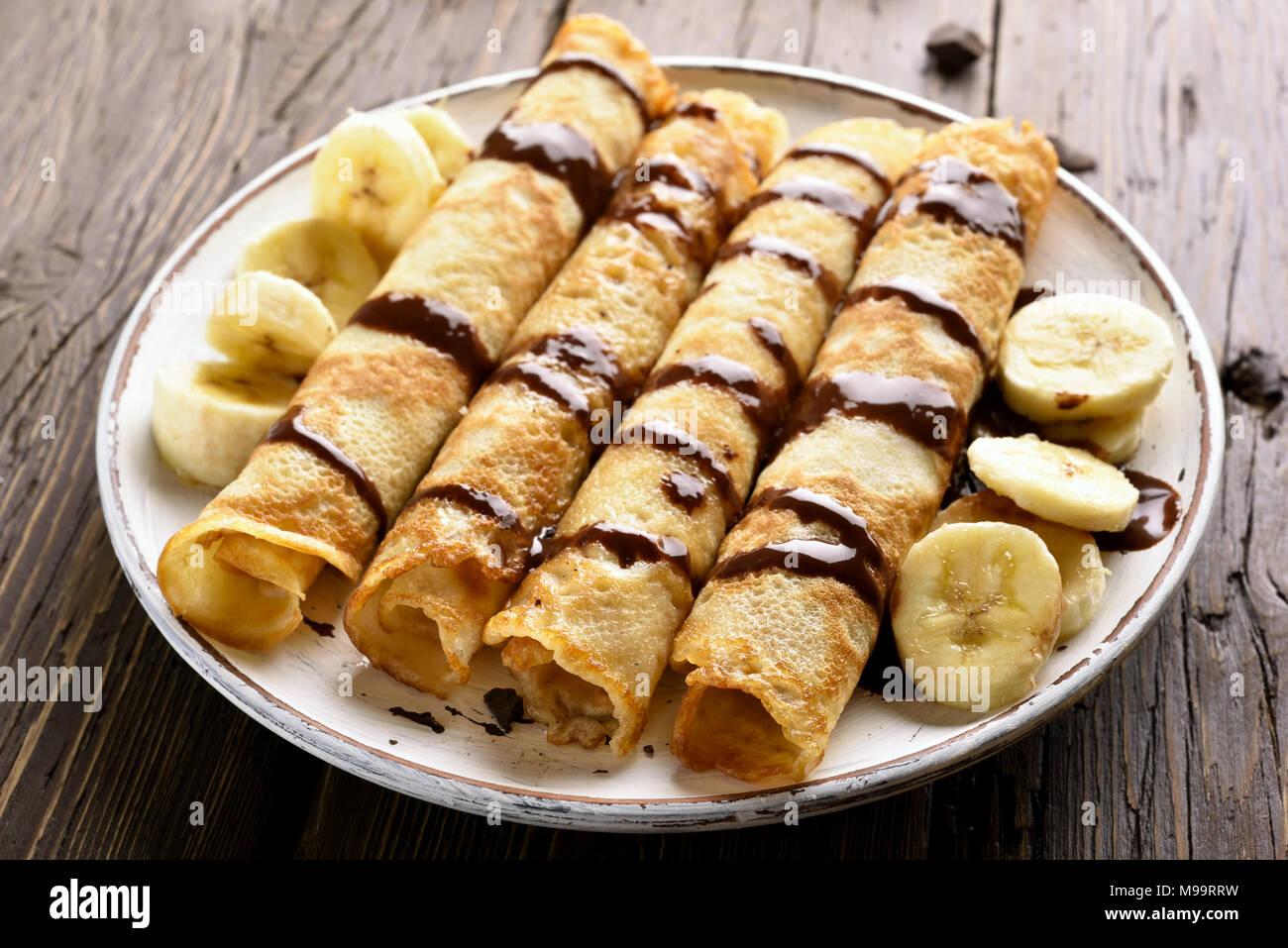Leckere Crêpe-Rolle mit Bananenscheiben und Schokoladensauce auf Holz- Hintergrund. Nähe zu sehen. Stockbild