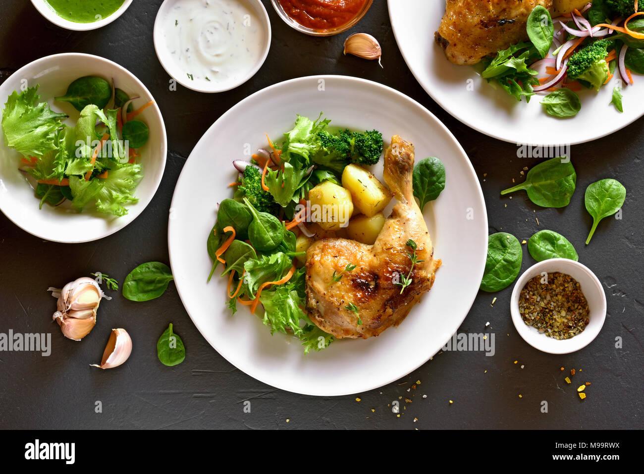 Leckeres gebackenes Huhn Bein mit Kartoffel- und grünem Salat. Gericht zum Abendessen. Ansicht von oben, flach Stockbild