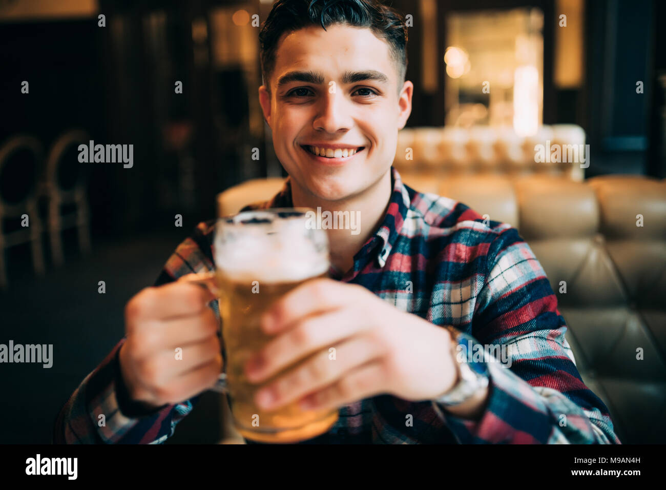 Man Bier trinkt. Junger Mann, Trinken, Bier, während Sitzen an der Theke Stockbild