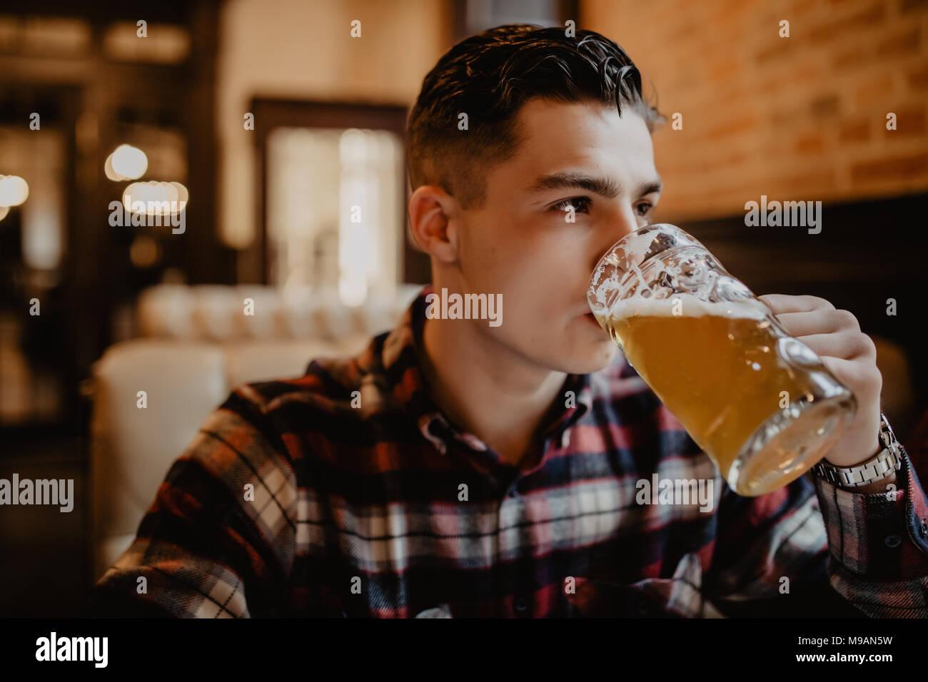 Ein junger Mann mit einem Bier in einer bar Stockbild