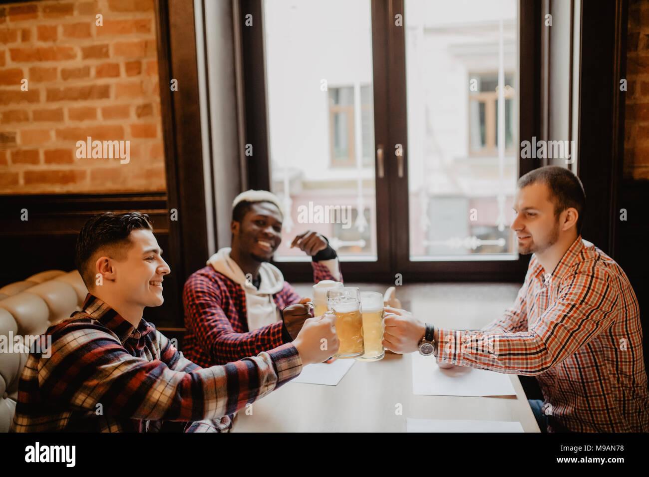 Stattliche Kerle sind klirrenden Flaschen Bier, Kamera und lächelnd, während im Pub ruhen Stockbild