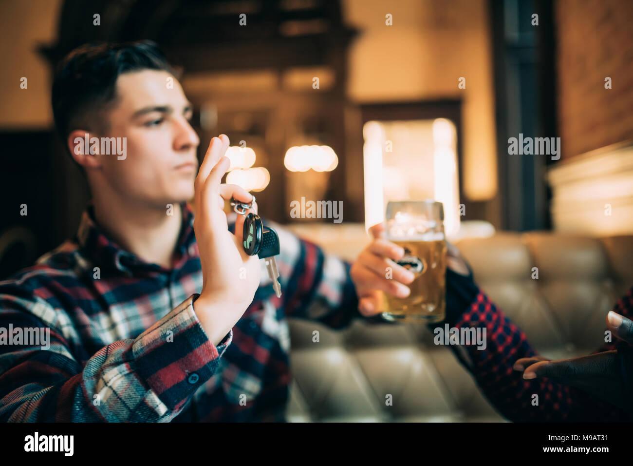 Junger Mann hält Autoschlüssel und die Ablehnung von Bier aus seinem afro-amerikanische Freund zu trinken Stockbild