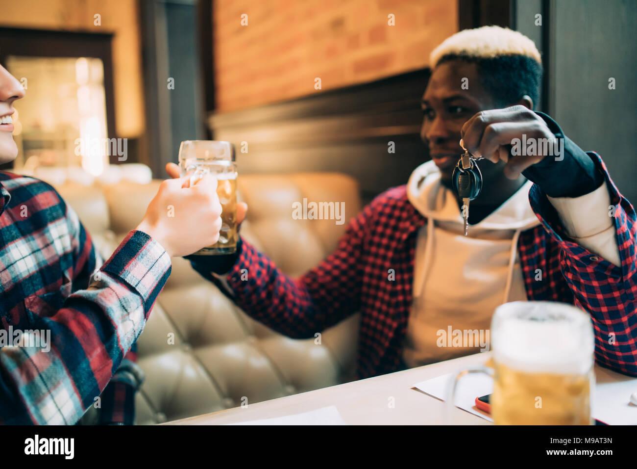 Junge afro-amerikanische Mann hält Autoschlüssel und die Ablehnung von Bier aus seinem Freund in der Kneipe zu trinken. Nicht trinken und fahren. Stockbild