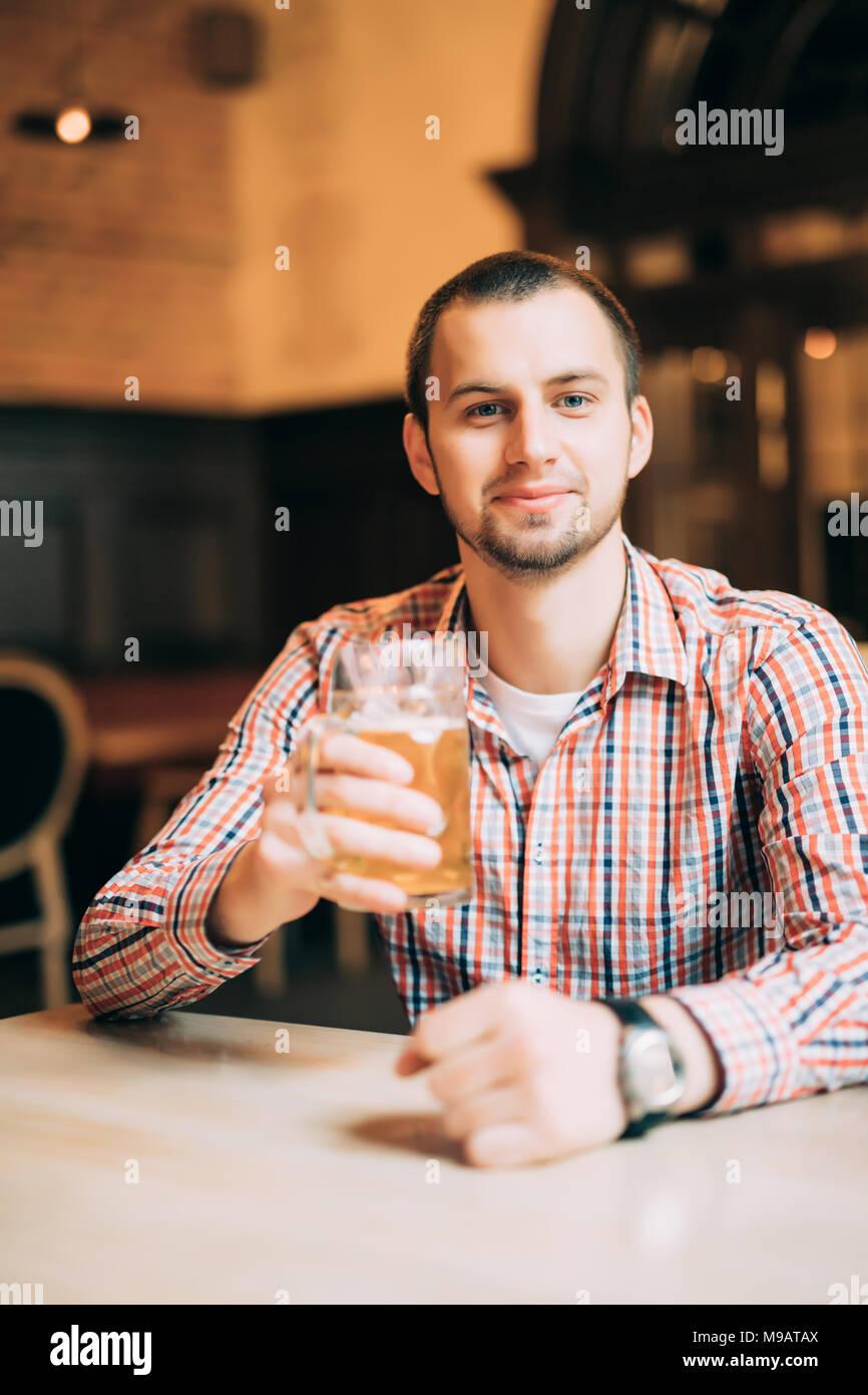 Hübscher junger Mann trinken helles Bier in einem Pub Stockbild