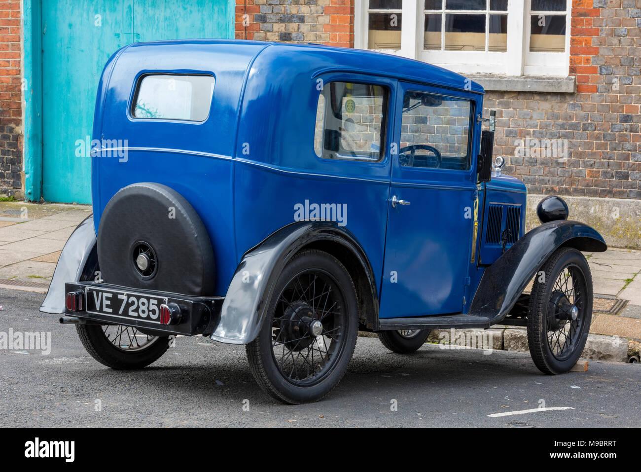 Ein vintage Austin Auto in Blau im Alltag an der Seite der Straße geparkt. Retro Vintage Sammler Auto mit Speichenrädern jeden Tag verwendet wird. Stockbild